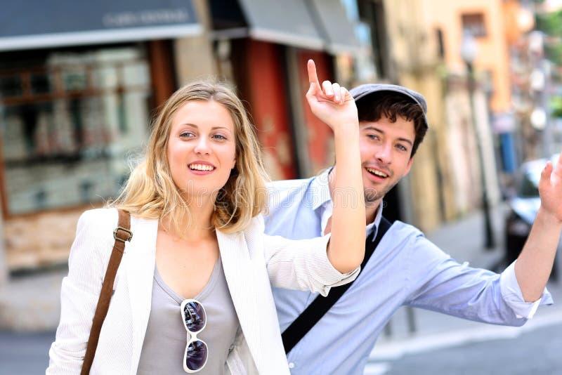 Pares novos que chamam o táxi na rua fotografia de stock royalty free