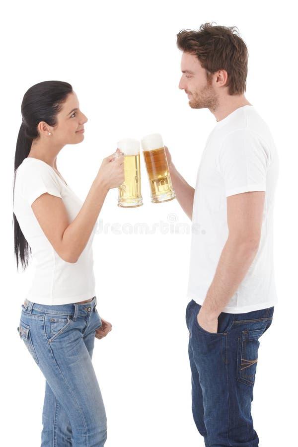 Pares novos que clinking com as canecas de sorriso da cerveja imagem de stock royalty free