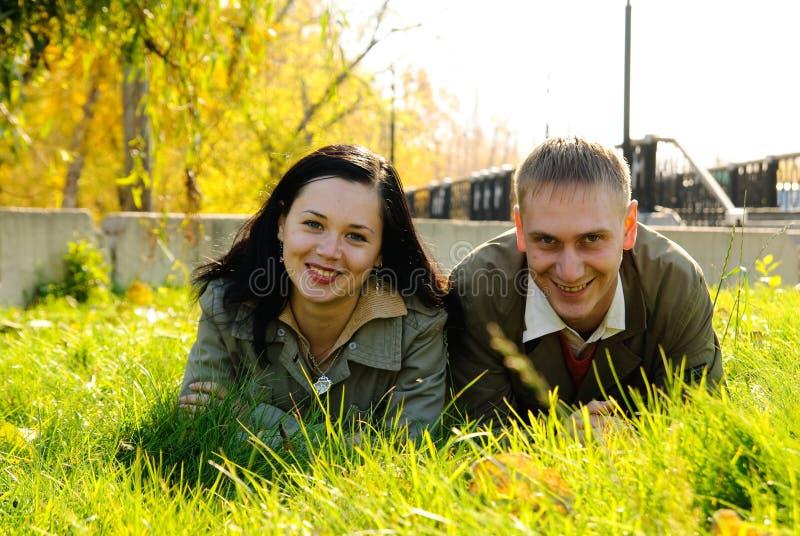 Pares novos que colocam na grama verde fotografia de stock