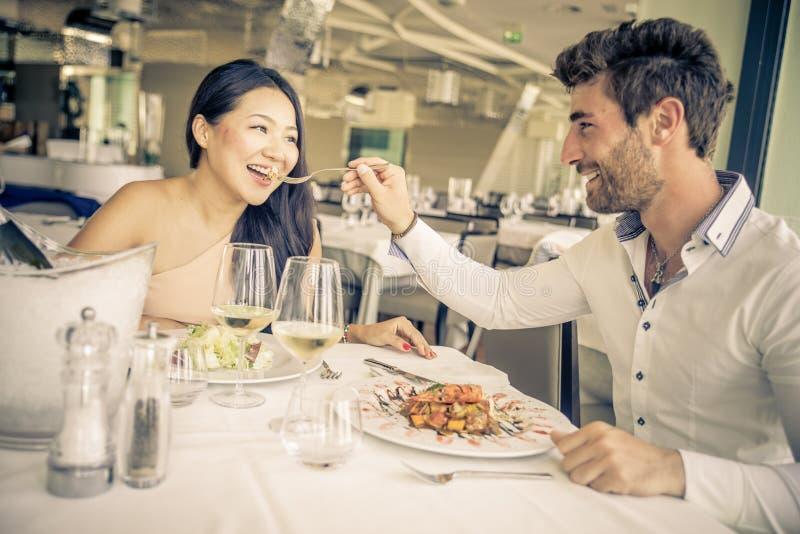 Pares novos que comem em um restaurante fotos de stock