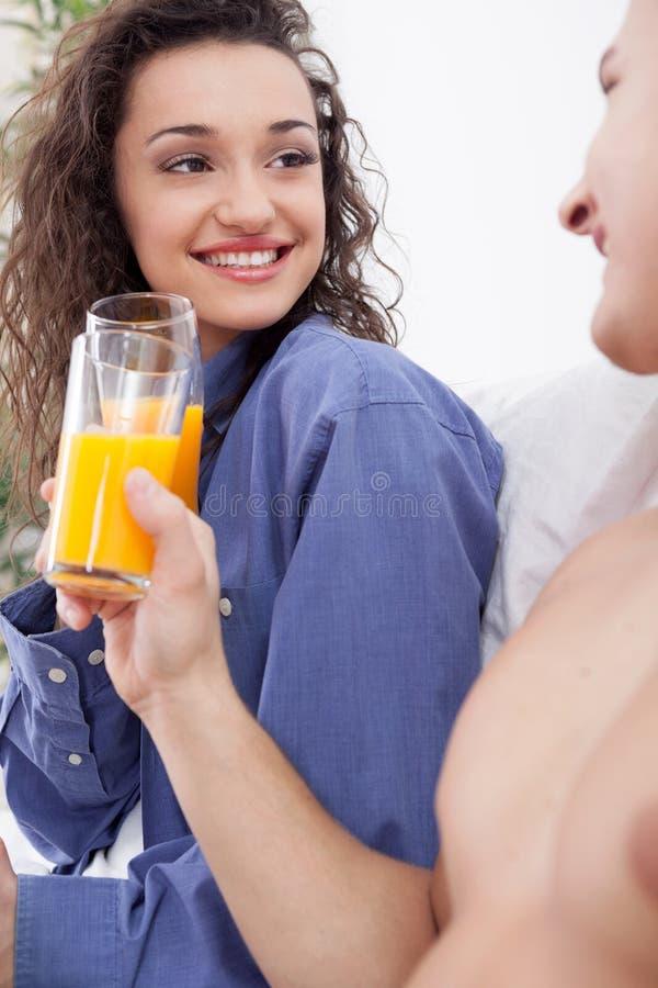 Pares novos que comem o café da manhã na cama junto foto de stock royalty free