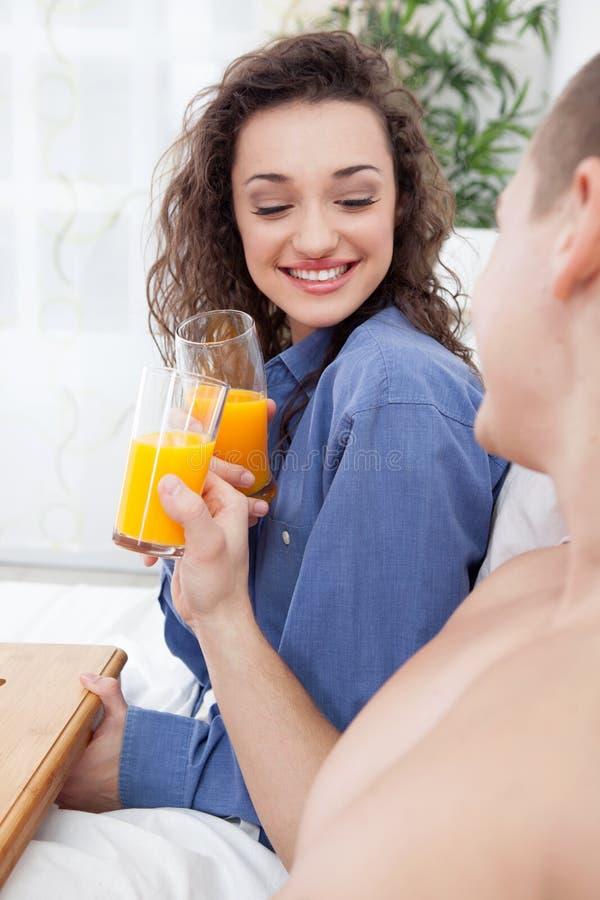 Pares novos que comem o café da manhã no brinde da cama com suco de laranja imagem de stock