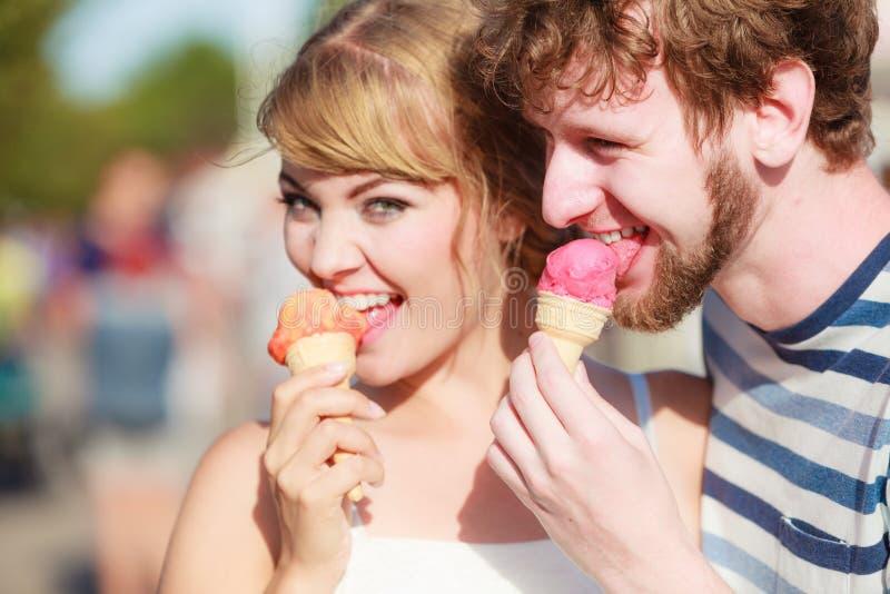 Pares novos que comem o gelado exterior imagens de stock royalty free