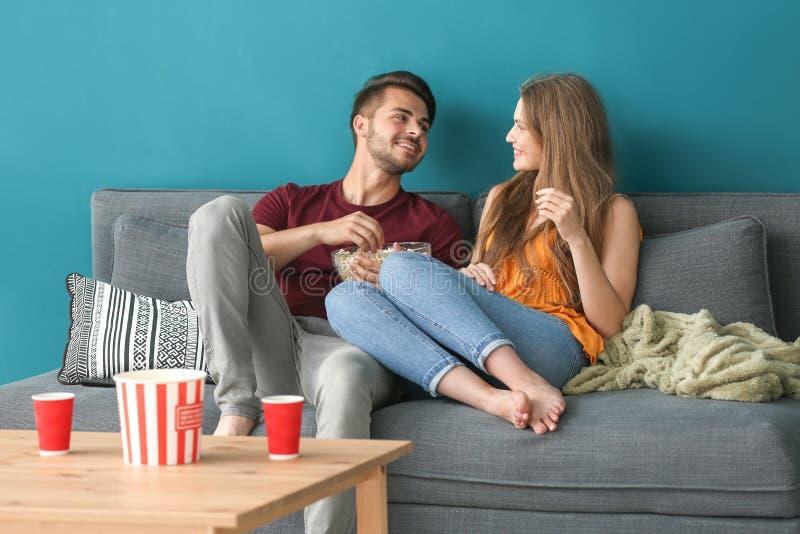 Pares novos que comem a pipoca ao olhar a tevê no sofá em casa foto de stock