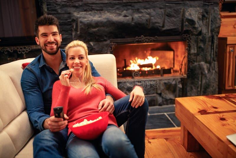 Pares novos que comem a pipoca e que encontram-se no watchi do sofá em casa imagens de stock royalty free