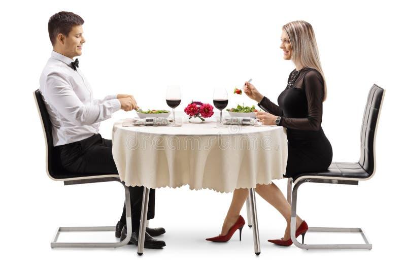 Pares novos que comem a salada e o vinho em um restaurante fotografia de stock