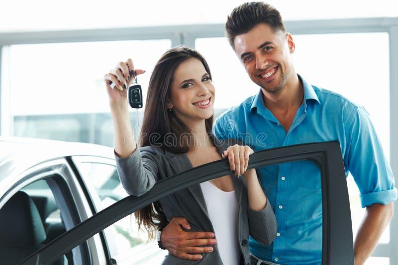 Pares novos que comemoram a compra de um carro na sala de exposições do carro foto de stock