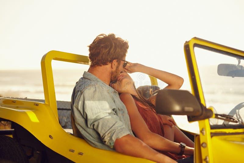 Pares novos que compartilham de um momento romântico quando em uma viagem por estrada foto de stock royalty free