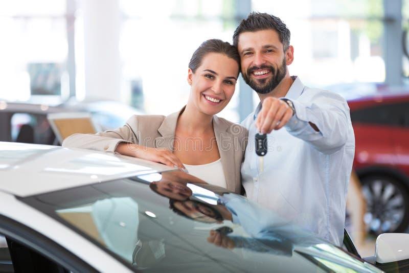 Pares novos que compram um carro fotografia de stock royalty free