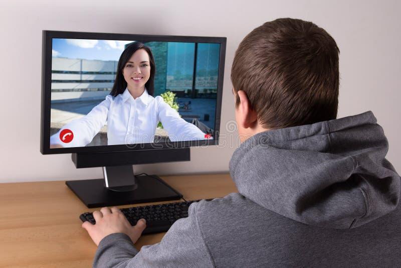 Pares novos que conversam sobre uma chamada video imagens de stock royalty free