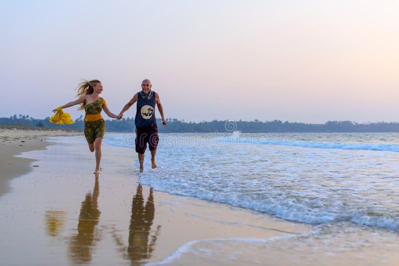 Pares novos que correm em conjunto na costa de mar Indivíduo de riso e menina magro 'sexy' que movimentam-se no surfline Conceito foto de stock royalty free