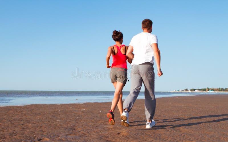 Pares novos que correm junto ao lado da água na praia Homem imagem de stock royalty free