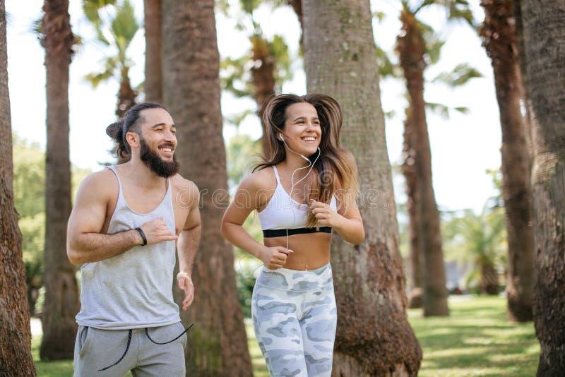 Pares novos que correm no parque na manhã do verão imagem de stock royalty free