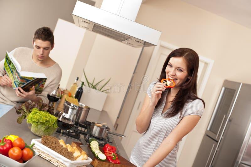 Pares novos que cozinham na cozinha moderna foto de stock