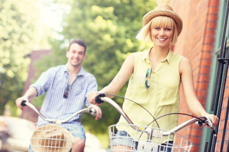 Pares novos que dão um ciclo junto na cidade foto de stock royalty free
