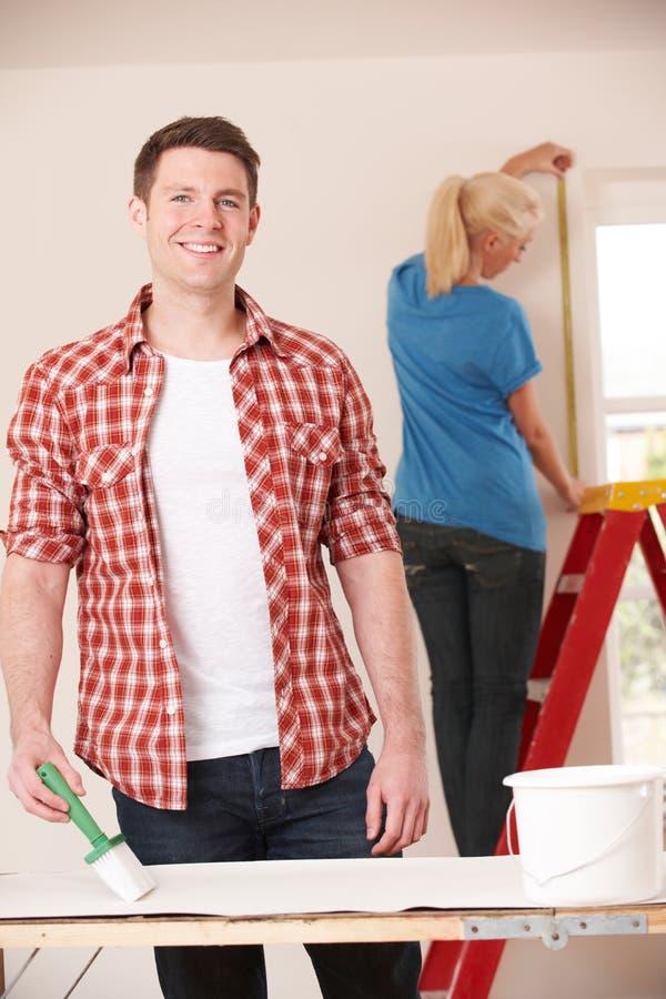 Pares novos que decoram a casa nova junto imagem de stock royalty free