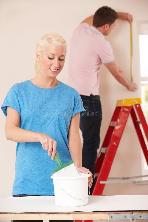 Pares novos que decoram em casa junto imagem de stock