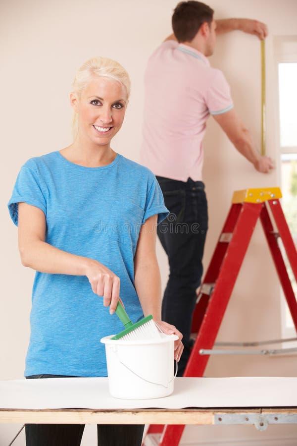 Pares novos que decoram em casa junto fotografia de stock
