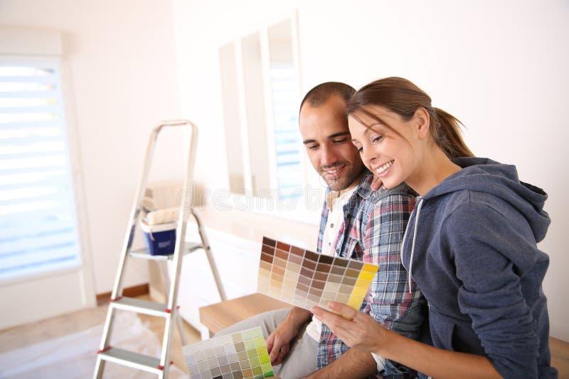 Pares novos que decoram sua casa nova fotos de stock royalty free
