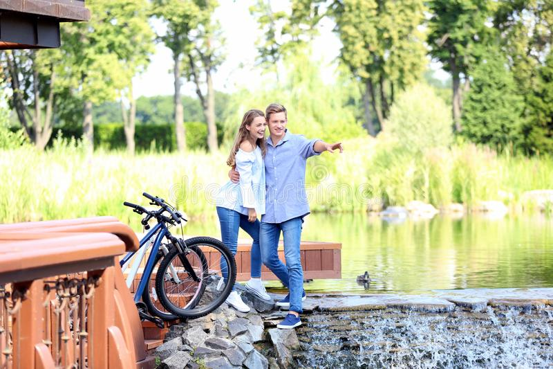 Pares novos que descansam perto do rio após ter montado bicicletas imagens de stock royalty free
