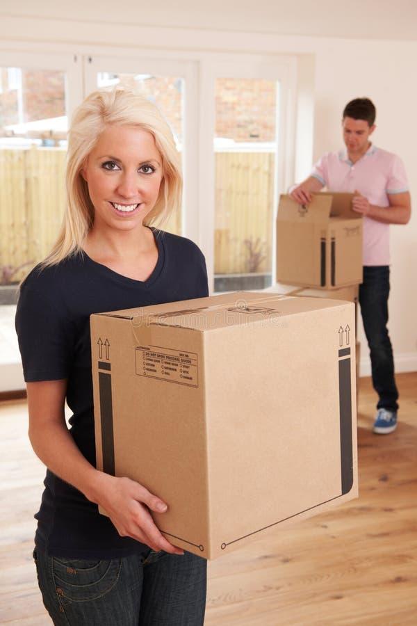 Pares novos que desembalam caixas na casa nova imagem de stock royalty free