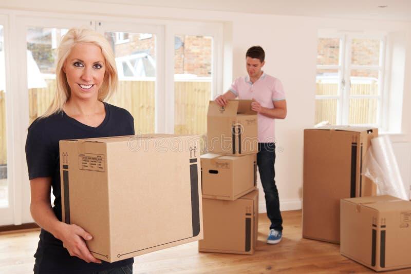 Pares novos que desembalam caixas na casa nova imagens de stock royalty free