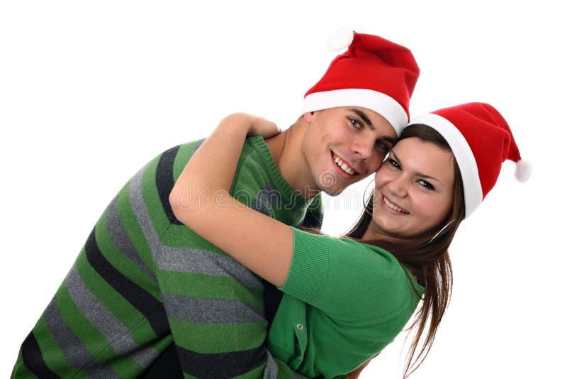 Pares novos que desgastam os chapéus de Santa que abraçam-se imagem de stock
