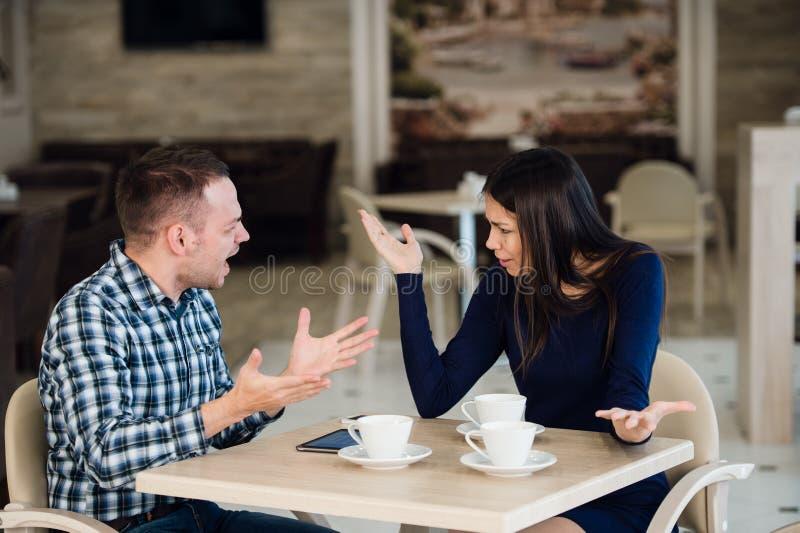 Pares novos que discutem em um café O ` s teve bastante, noivo se está desculpando Problemas do relacionamento foto de stock royalty free