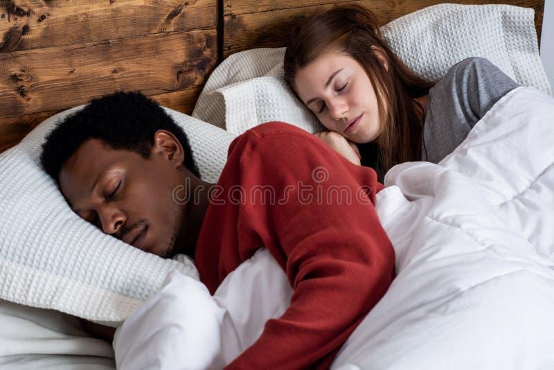 Pares novos que dormem em uma cama foto de stock royalty free