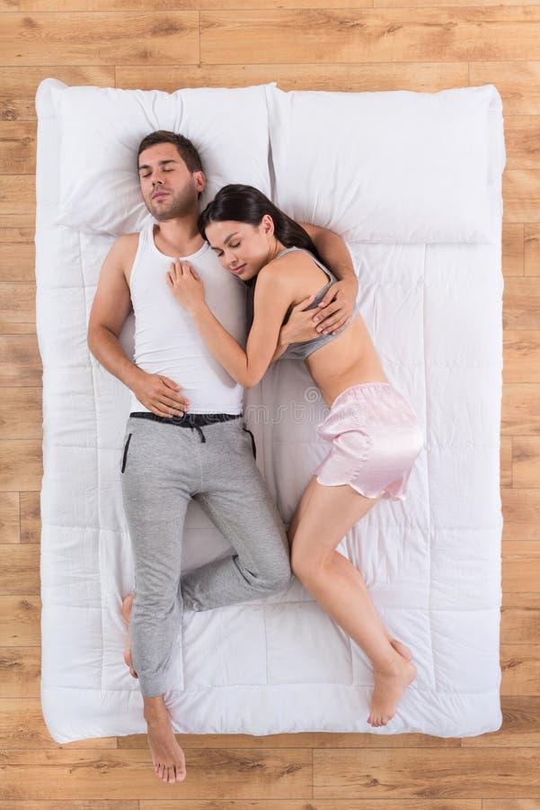 Pares novos que dormem junto na cama fotografia de stock royalty free