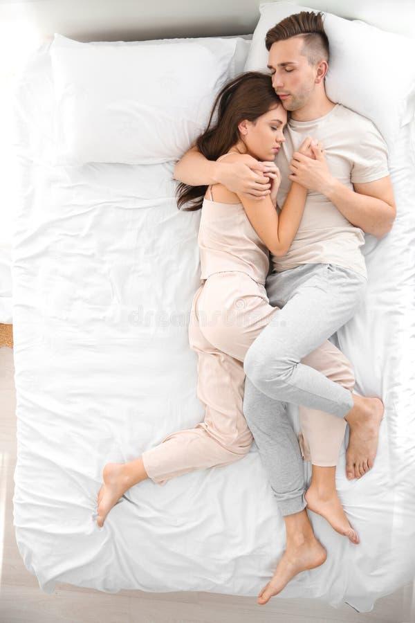 Pares novos que dormem na cama em casa foto de stock royalty free