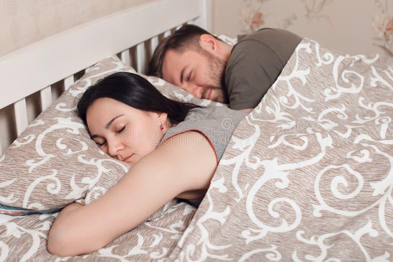 Pares novos que dormem na cama sob a cobertura imagens de stock royalty free
