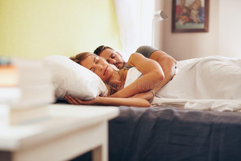 Pares novos que dormem pacificamente na cama fotos de stock royalty free