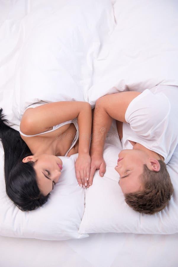 Pares novos que dormem sob a cobertura branca fotografia de stock