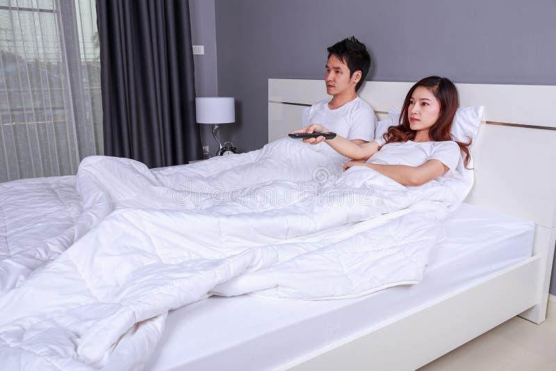 Pares novos que encontram-se em uma cama com o telefone do controlo a distância e da observação imagens de stock