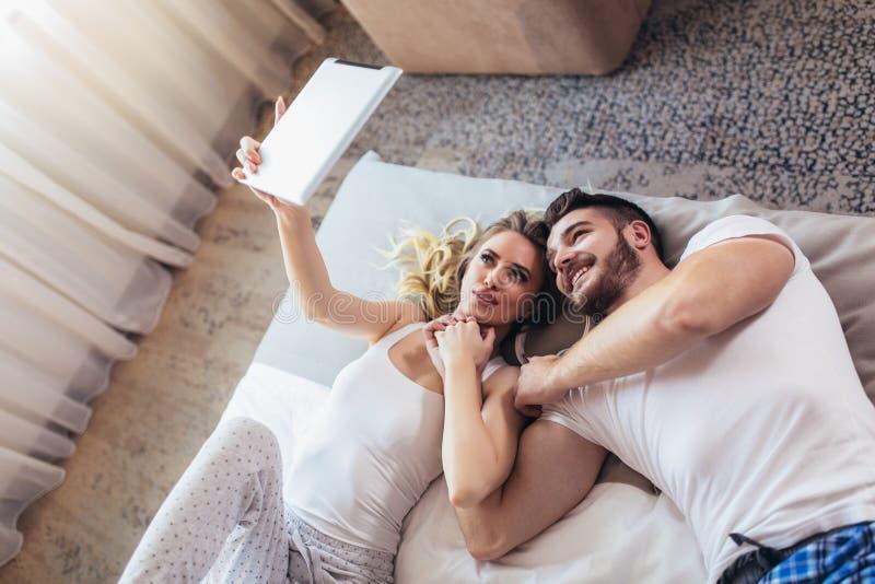 Pares novos que encontram-se na cama em um quarto e que usam a tabuleta digital foto de stock royalty free