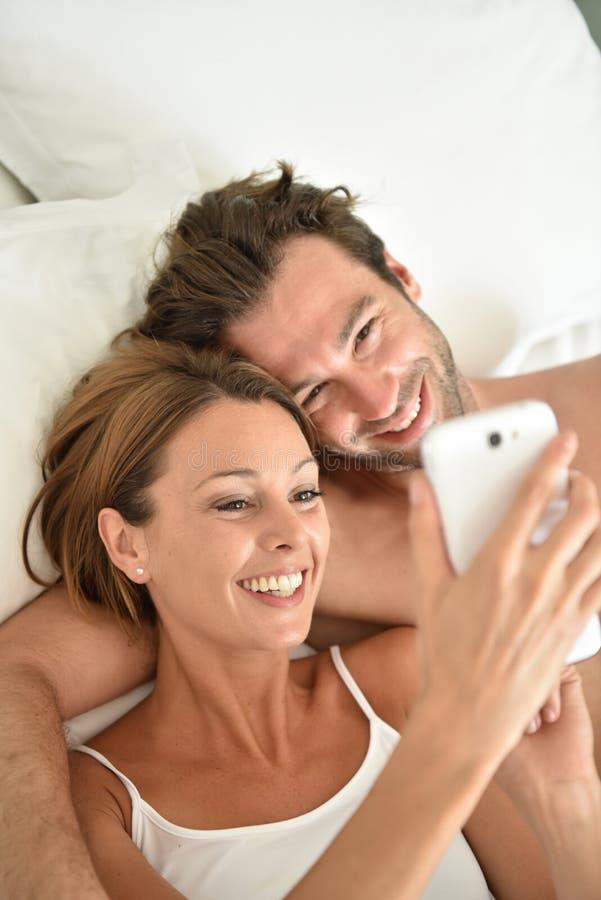 Pares novos que encontram-se na cama usando o smartphone fotos de stock royalty free