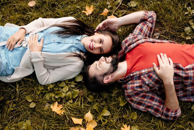 Pares novos que encontram-se na grama no parque do outono, cabeça foto de stock royalty free