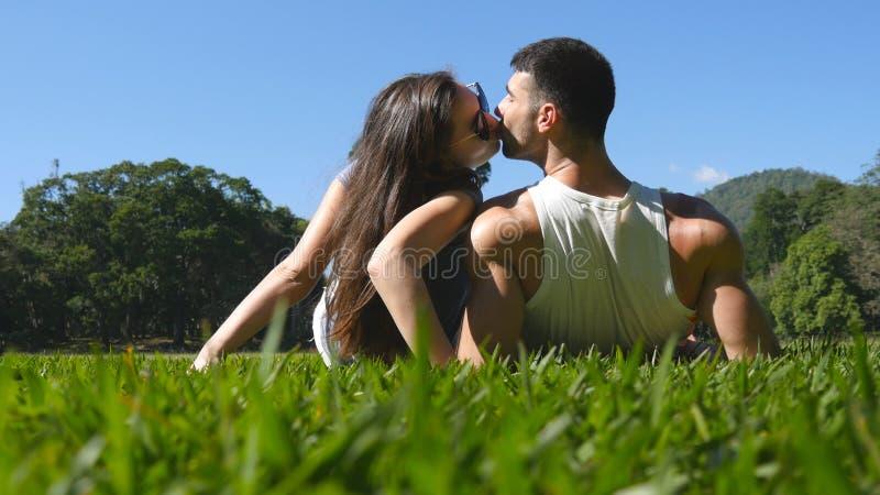 Pares novos que encontram-se na grama verde no parque e que relaxam Homem e mulher que sentam-se no prado na natureza e no beijo  imagem de stock