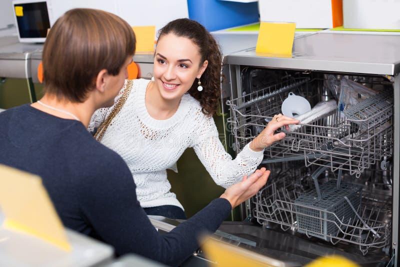 Pares novos que escolhem a máquina de lavar nova do prato no supermercado imagem de stock