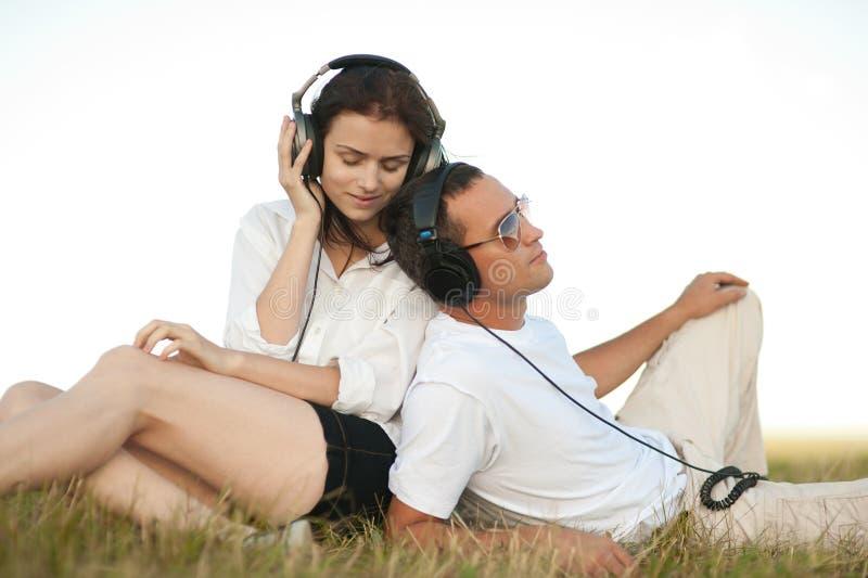 Pares novos que escutam a música fotos de stock