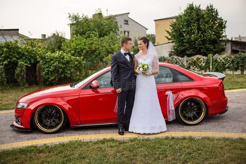Pares novos que estão na frente de um carro vermelho e que olham se imagens de stock