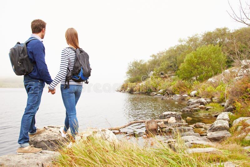Pares novos que estão por um lago que admira a vista imagens de stock