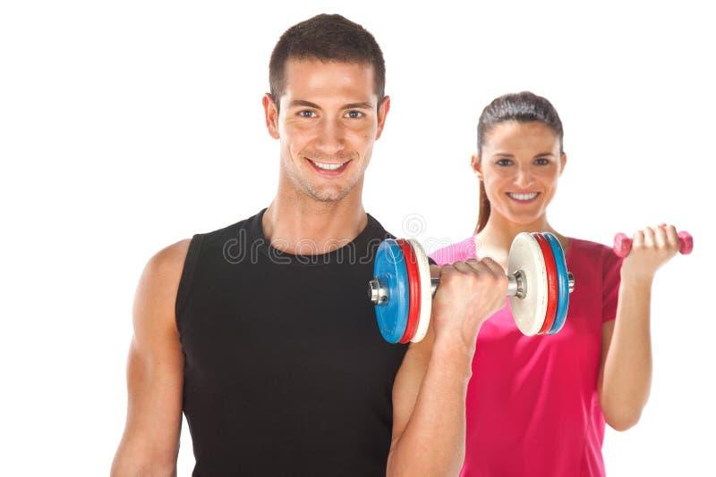 Pesos de levantamento do homem novo e da mulher. Isolado no branco foto de stock