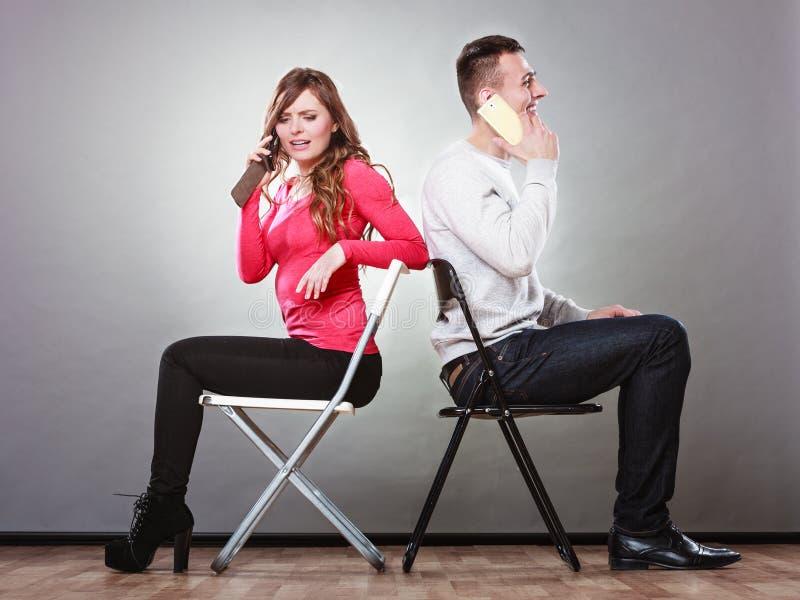 Pares novos que falam em telefones celulares fotografia de stock