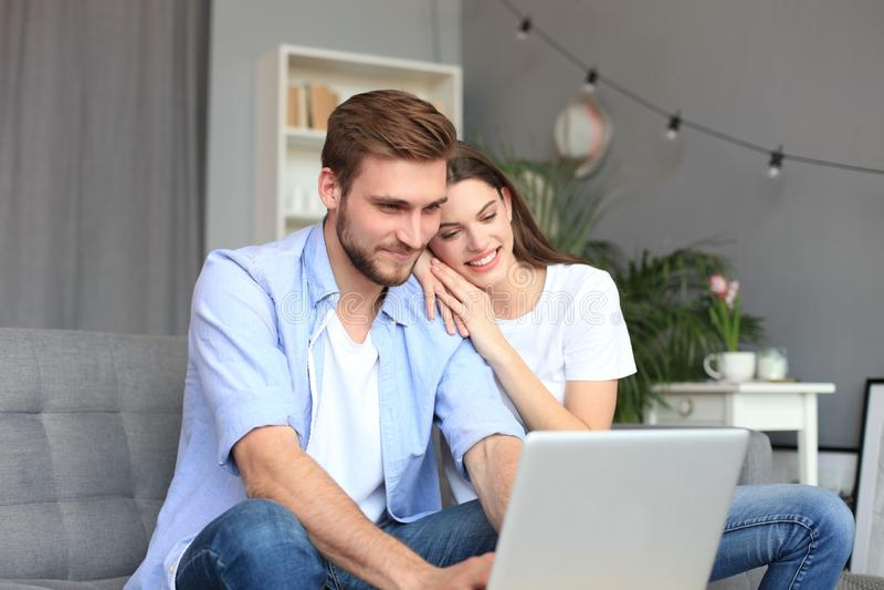 Pares novos que fazem alguma compra em linha em casa, usando um portátil no sofá imagens de stock royalty free