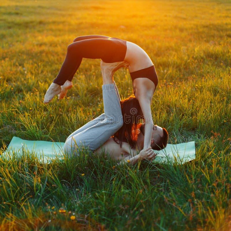Pares novos que fazem a ioga fora da cidade na grama foto de stock