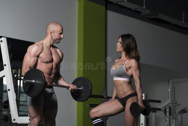 Pares novos que fazem o exercício pesado para o bíceps foto de stock