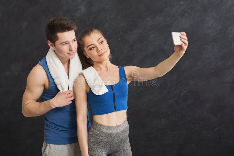 Pares novos que fazem o selfie no gym imagem de stock royalty free