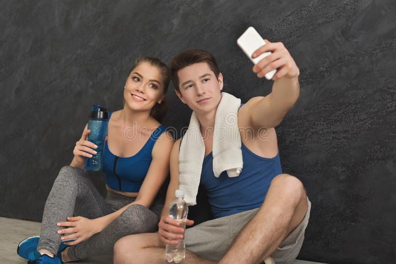 Pares novos que fazem o selfie no gym foto de stock
